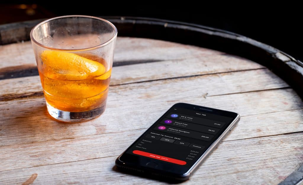 customer controls payments cell phone contactless payment app open with cocktail