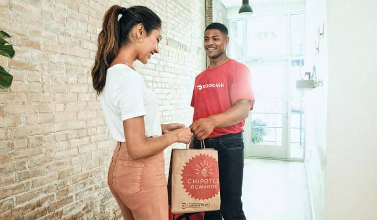 Doordash delivery driver man handing chipotle order to woman at doorstep