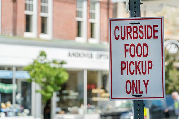 street sign in front of restaurant that says curbside food pickup only