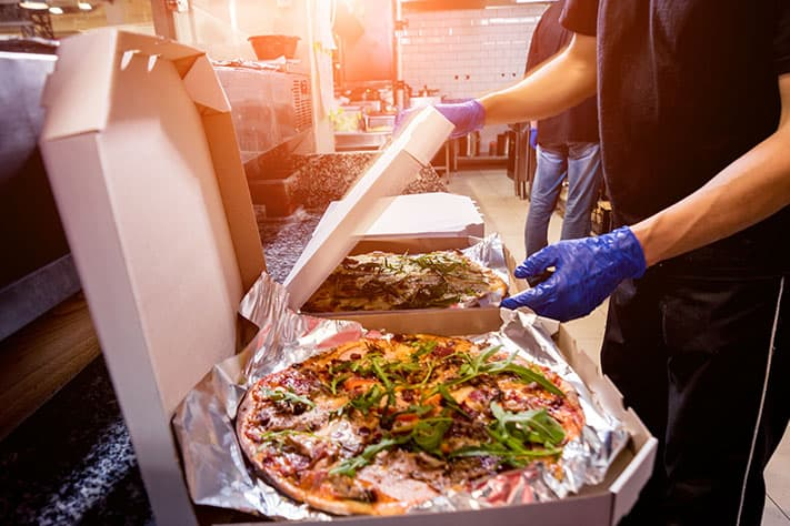 kitchen employees wearing gloves putting toppings on pizza kitchen line in ghost kitchen