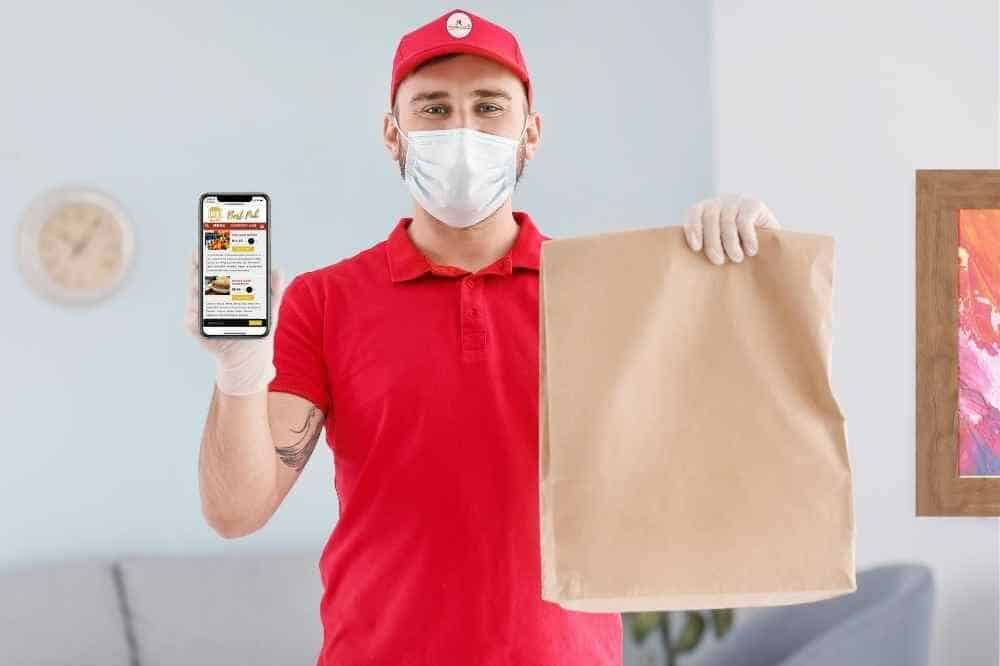 delivery driver wearing facemask holding cell phone with online ordering app open