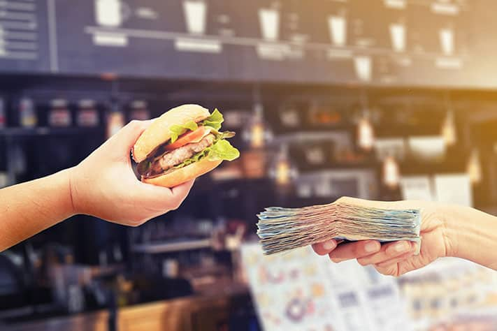 hand exchanging burger concept for hand exchanging cash showing benifts of virtual kitchen